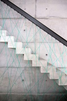 From MO Architekten, concrete stairs with cord crisscrossing to form the sides of the railing — yes please! Just think of all the fun colors you could string when you get bored with this one.