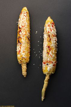 Elote Asado- Mexican street food - grilled corn spread with mayonnaise, rolled in cheese, and sprinkled with chili powder. By la Domestique