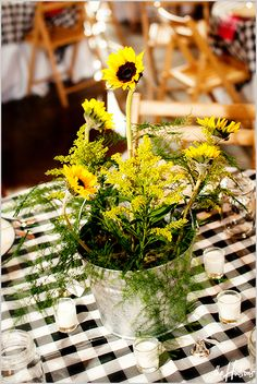 Black and white checkered tablecloths and potted sunflowers for a country-themed barn wedding - Photo by Jason