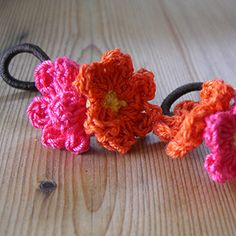 Tiny crocheted flowers sewed onto pony tail holders.  Awesome!