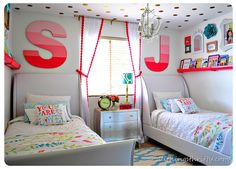 curtains with pom trim, bold letters and dots on ceiling, picture frames above shelf, and bedding.