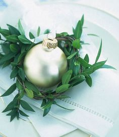 At each place setting, greenery and an ornament to give to each guest at your Holiday table. You can personalize the ornament as a place card...and it's a great memory for years to come...!
