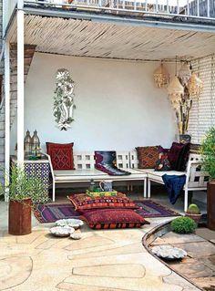 terrasse de style marocain décorée de coussins de sol en rouge et pourpre et aménagée avec une pergola en bambou