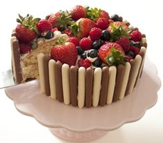 Vanilla cake surrounded by white and milk chocolate fingers and topped with strawberries, raspberries, and blueberries