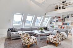 Un ático con vigas vistas y ventanas tragaluz en el tejado