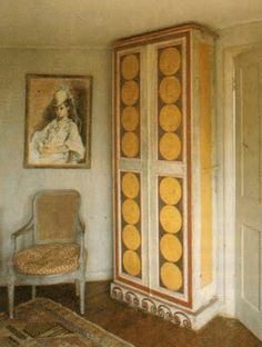 Vanessa Bell's bedroom at Charleston, with cupboard decorated by Vanessa Bell. On the left of the cupboard is a portrait of Vanessa Bell's daughter, Angelica, painted by her father Duncan Grant