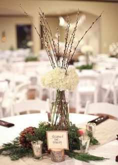 Beautiful, rustic winter centerpiece by Signature Flowers from our winter featured wedding. Photo by Aaron Snow Photography. #wedding #tall #centerpiece #white #green #winter #rustic