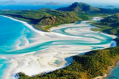 Whitehaven Beach at Whitsunday Island in Australia. This beach is known for its beautiful white sands and the crystal clear blues and greens of the water. The sand is very fine and walks along the shore are so fantastical it seems like magic.