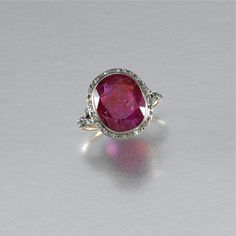 RUBY AND DIAMOND RING, EARLY 20TH CENTURY Collet-set with an oval ruby within a border of single-cut diamonds to similarly-set stylised foliate shoulders