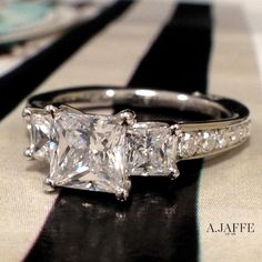 A.JAFFE Art Designed Princess Artistic Three Stone Engagement Ring (ref: MES591).  What would you name this ring?