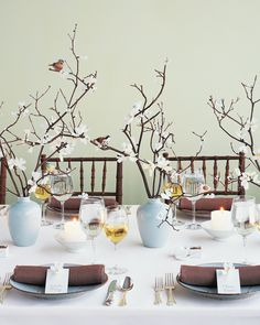 Fit for a spring wedding, these branches bloom with handmade paper blossoms and are accented with millinery birds.