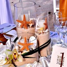 A cute beach wedding centerpiece idea with sand, candles, starfish and shells.