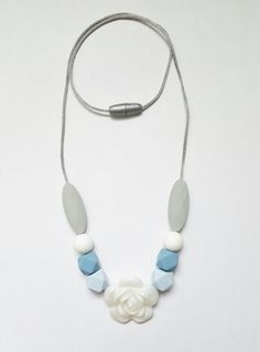 Silicone teething necklace with grey, blue and white beads along with a flower bead, for baby and mom. Made of baby chew-safe food grade silicone and perfect as a nursing necklace too.