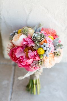 SO MUCH PRETTY IN ONE BOUQUET: coral peony, succulent, silver brunia, rice flower, ranunculus, protea, billy balls, spray rose, juliet garden rose, green thistle, scabiosa pod.