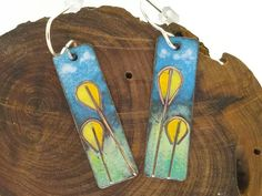 This charming pair of earrings features abstract yellow flowers in the foreground, with a distant meadow and blue skies in the background. The flowers are made from copper wire embedded into the glass enamel. I created this tiny cloisonne painting by meticulously applying various colors of very fine glass enamel powder onto a canvas of copper using small brushes, then firing it in a kiln until the glass powder melts and fuses itself to the copper. The finished result is a compact piece of…