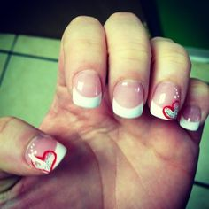Cute French Tip Manicure with Red Hearts Look at how cute these french tips look with the red sparkly hearts. The base of this manicure is your common french tip manicure which looks very good. There is also some type of shine on this, we will assume it i a shiny top coat on top of all the nails. Now two of the nails have these cute little hearts drawn on top of them which turns this into a perfect manicure for romance. Valentine's Day or any other romantic day, these are the nail you want…