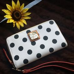 Dooney and Bourke extra large wristlet This darling wristlet is white leather with black dots for a colorful and playfulness that you will adore. Lined with red fabric and has a detachable wristlet strap. Retails $108 Dooney & Bourke Bags Clutches & Wristlets