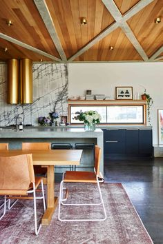This modern statement kitchen is serious goals. Love that crazy gold brass hood and those leather dining chairs.