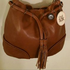 "The Sak Indio leather Tag says ""Indio Leather, Tob Belted"" and features a drawstring belt with fringe tassels. Beautiful tobacco color brown.?  Purse opens and closes with a snap. Inside is a long zippered pocket which divides the purse into two sections. There are additional pockets inside and also a slip pocket on outside of purse (on back of purse). Very pretty fabric lining and silver tone hardware.  Nice size with height approx. 12.5"" and width approx. 16"" across the middle and 13""…"