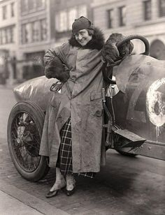 Elinor Blevins beside her race car. 1915