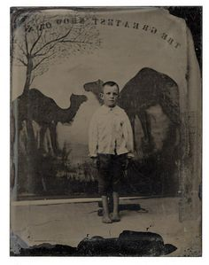 Barefoot Boy (supported by stand to help him maintain his pose for the duration of the photography session) with Camels Backdrop. Either this picture was reversed, or the camels were hung backwards (see words above them).