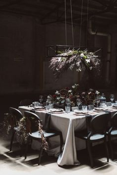 For a bold floral focal point, In Bloom Florist draped a rectangular iron chandelier with white lilies and 'After Dark' willow myrtle. | Photo by Jessica Connery Photography