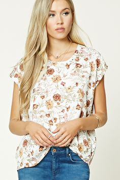 A woven top featuring an allover floral print, boxy silhouette, a round neckline, and short sleeves.