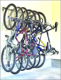 Storing a lot of bikes (I count 6 here!) in a small garage on the wall.