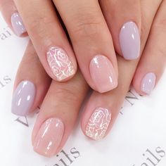 Brides.com: . A lavender-and-pink manicure with white roses on the ring finger and glitter on the middle finger.