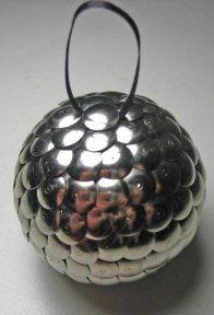 This scale-textured ornament sparkles and shines perfectly for the holidays. Its metallic armored look is achieved with - wait for it - flat-headed metal thumbtacks...