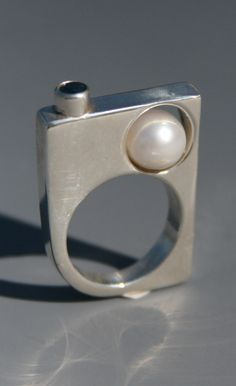 Craig Moore: cast sterling silver ring with a white pearl and topaz set stone.