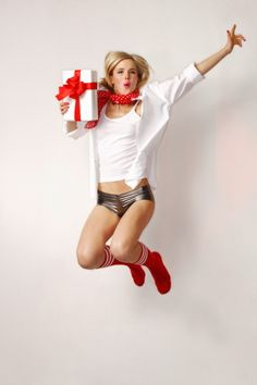 Blond woman with gift parcel cutting a caper