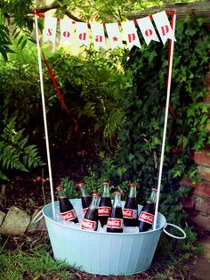 Summer Party Soda Pop decor - Make your cooler of drinks part of the decor by creating a fun soda stand. Prepare two wooden dowels of the same length by screwing an eyehook into the ends. Prop them up in a bucket full of ice and bottled drinks, and hang a paper banner between the two dowels. Now everyone will definitely know where to go for ice-cold drinks. Design and photography by Olivia Kanaley of A Field Journal