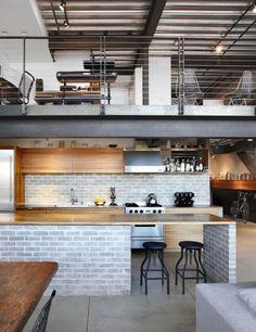 No teto deste apartamento, estrutura metálica e canos pretos expostos. Destaque para o vão que, criado a partir da bancada, dá espaço à mesa.
