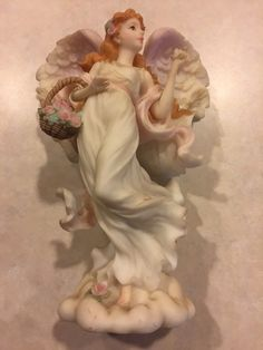 Angel holding rose and carrying basket full of flowers. Red marks on base near rose. | eBay!