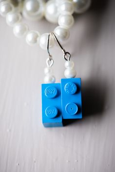 Handmade LEGO earrings for the bride and her bridesmaids for this LEGO themed wedding. Easy DIY if you have a small drill and some pliers!   Want your wedding planner to help you with details like these? Check out www.thistlebea.com  Credit to Jelger & Tanja Photographers