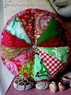rundes Kissen aus mindestens 12 verschiedenen Stoffen im Farb-, Material- und Muster-Mix genäht und weich gefüllt mit 100 % Polyesterfasern. In der Mi
