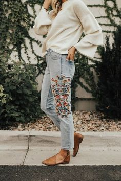 Embroided blue jeans with a flowy white sweater top