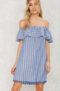 You might as well look like you're on vacation. The Tulum Dress is made in a faded blue cotton-linen blend and features a black and white striped pattern, elastic at neckline, off-the-shoulder design with ruffle, darkened fringe at hem, and side pockets - get even more style and shopping inspiration on http://jojotastic.com/shop-my-favorites/