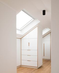 Minimal finishes are used throughout the interiors of this loft conversion, including white-painted walls and light wooden flooring.