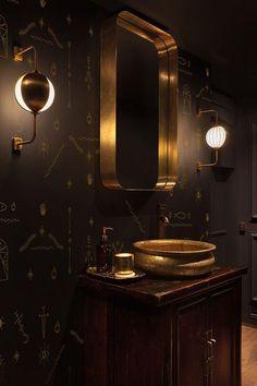 Dunklen Holzschrank, schwarzen gemusterten Wänden und Messing Dekorationen
