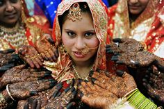 An Indian Muslim bride smiles as other brides pose with their hands adorned with henna art before the start of a mass wedding in Ahmedabad on March 21, 2010. Some 201 Muslim couples participated in a mass wedding organised by The Gujarat Sarvajanik Welfare Trust