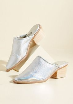 You definitely return for a follow-up trot in these silver mules! Touting real wooden heels in a light pine hue, and soft leather uppers and sturdy leather soles, this metallic-coated pair will find its way onto your feet time and time again.