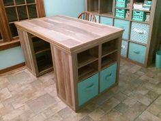 Craft room desk finished. Started with two Better Homes & Gardens 4-cube units. Added a plywood top and laminate flooring on top of that. Trim pieces around the top edges to cover the edge of the plywood and flooring. Thanks to my awesome hubby for such a wonderful craft table!