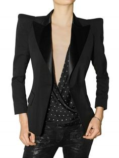 Black wool tailored jacket by Balmain featuring angular peaked shoulders. The jacket has a satin collar with wide lapels and a one-button front closure. It has two flap-top front pockets and four-button details on the cuffs.