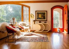 Pickles, the Honey family's shih tzu, stands watch over a pair of Bertoia chairs topped with sheepskins in the entry.