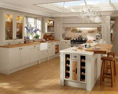 cream kitchen units and wooden worktop, also like the wine rack