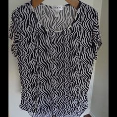 Plus- Zebra Print Blouse Black and White 1X Take a walk on the wild side with this hot top!  Black and white zebra print.  Make a statement with this solo with a pair of jeans and heels or under a black blazer for work.  26 inches long.  95%polyester/5% spandex for just the right amount of stretch. TNO Tops Blouses