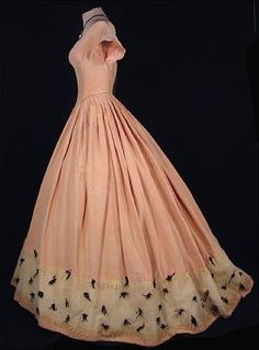 """(circa Pale pink silk moire ballgown with sweep hemline. Extremely fitted bodice, pointed """"v"""" waist, off-the-shoulder neckline, scalloped cap sleeves, ivory tulle and lace band around skirt bottom dotted with black velvet baby ribbon bows. Back lacing. Civil War Fashion, 1800s Fashion, 19th Century Fashion, Victorian Fashion, Vintage Fashion, Victorian Dresses, Steampunk Fashion, Emo Fashion, Victorian Gothic"""
