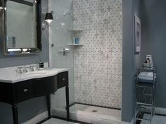Tile from the tileshop.com. chic black bathroom vanity sink, beveled mirror, marble countertop, blue gray walls paint color and marble basketweave tiles shower surround.